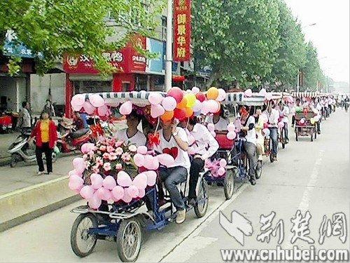 由16辆四轮自行车组成的迎亲车队从汉南街头驶过时,吸引了众多路人关注。