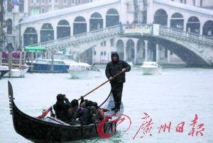 在意大利威尼斯大运河上,一名船夫在飘落的雪花中运送乘客。