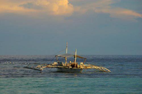 """海滩远处,停着几艘""""螃蟹船""""(Banga)"""